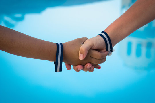 Kids hands shaking over blue water background. Stripes bracelets, all inclusive wristbands, hotel, resort, leisure time, holidays, summer vacation concepts