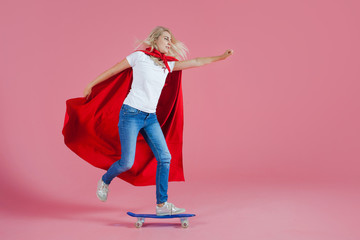 superhero on a skateboard. Funny young woman in the image of a superhero to the rescue