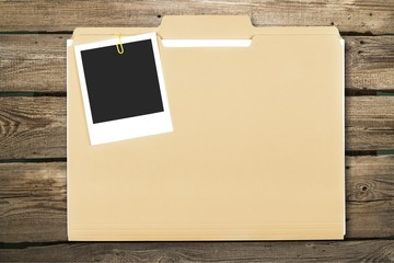 Blank photo on business folder on wooden