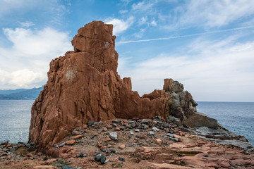 Red rocks of Arbatax city, Sardinia, Italy. Beautiful blue sky with some clouds and sea on a sunny summer day. Nobody in the scene.