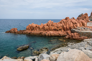 Red rocks of Arbatax city, Sardinia, Italy. Beautiful blue sky with some clouds and small beach on a sunny summer day. Nobody in the scene.