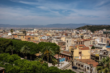View on the city of Cagliari, the capital of Sardinia, Italy. Colorful houses and blue sky on a sunny day, mountains in the background.