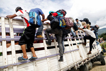 Honduran migrants, part of a caravan trying to reach the U.S., get off a truck during a new leg of their travel in Chiquimula