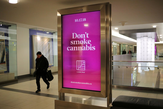 A shopper walks past an advertisement advising against the use of cannabis, the day before Canada's legalization of recreational marijuana, in Toronto