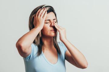 Fototapeta Sinus pain, sinus pressure, sinusitis. Sad woman holding her nose and head because sinus pain