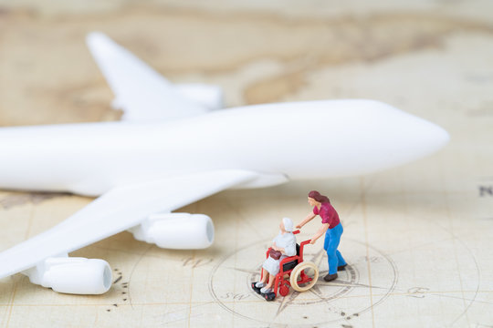 Medical trip planning or travel concept, miniature senior elderly people on wheelchair with son or caregiver standing with toy airplane on vintage world map with compass, next destination