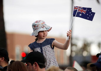 A child waves Australia's national flags during a community picnic with Britain's Prince Harry and his wife Meghan, Duchess of Sussex, at Victoria Park in Dubbo