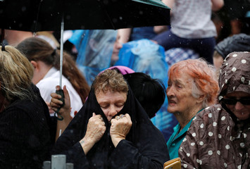 People shelter themselves from the rain during a community picnic with Britain's Prince Harry and his wife Meghan, Duchess of Sussex, at Victoria Park in Dubbo