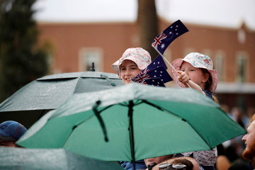 Children wave Australia's national flags during a community picnic with Britain's Prince Harry and his wife Meghan, Duchess of Sussex, at Victoria Park in Dubbo