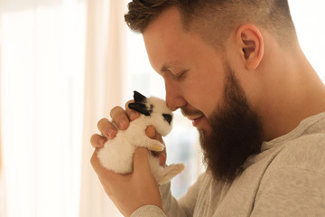 Bodybuilder with a little rabbit. Muscular man with a beard in a tight T-shirt holding a pet. Stylish and sporty young man loves his pet.