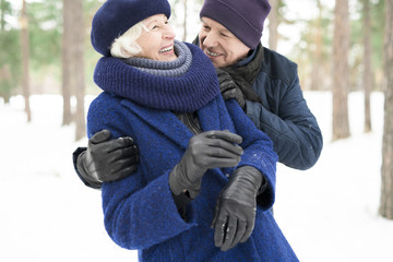 Waist up portrait of playful senior couple enjoying walk in winter forest