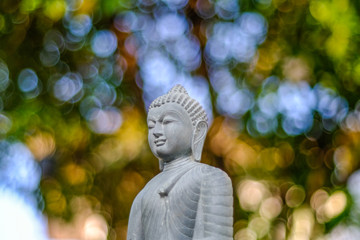 Focus on the Green Buddha and bokeh light background.