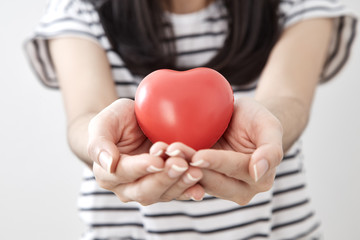 Young woman hand showing red heart