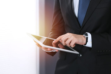 Unknown businessman holding digital tablet in office