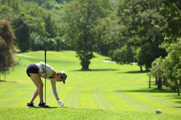 Asian woman playing golf on a beautiful natural golf course