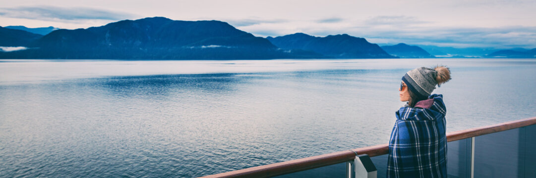 Alaska cruise travel luxury vacation woman banner panorama of inside passage scenic landscape background on balcony deck enjoying view of mountain range. Asian girl tourist with wool blanket.