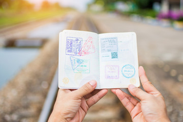 Hand holding passport show immigration stamps on passport with railway background. subject is blurred.