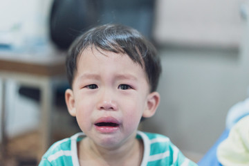 A sad boy is crying, he doesn't want to go to bed at night.