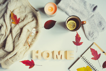 Wall Mural - autumn or winter feminine flat lay with cozy fashion knitted sweater and socks, hot tea and home wooden letters on white background