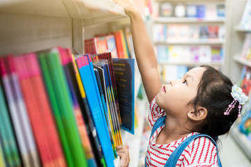 Cute asian child girl select book on bookshelf in bookstore in supermarket