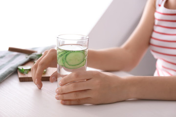Woman holding glass with tasty fresh cucumber water on light table