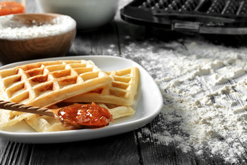 Plate with delicious waffles and jam on wooden table