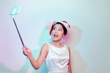 Beautiful happy asian woman in Santa Claus hat making selfie photo with phone