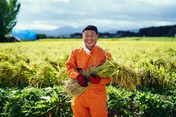 稲を持ち笑顔の男性