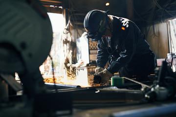 工場でサンダーを掛ける男性