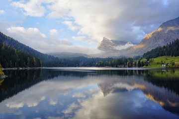 St Bernard lake, Switzerland, Grigioni canton. Sunset light with clouds reflected in the water Fototapete