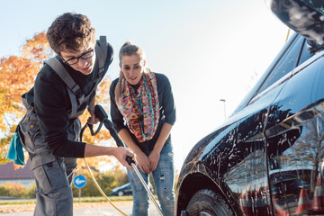 Service man helping woman cleaning her auto in car wash with nozzle
