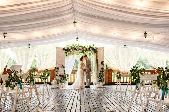 Wedding ceremony. Elegant wedding couple kissing near wedding arch, bride and groom in love