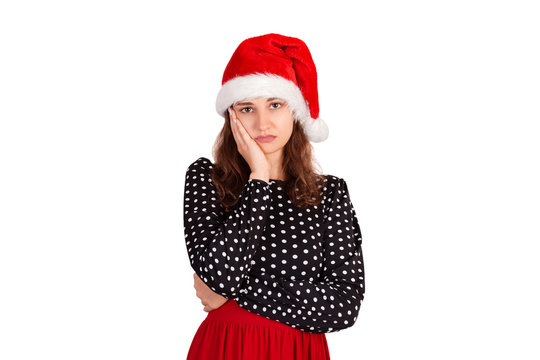 gloomy anxious good-looking woman in dress, frowning and being sad, having troubled. emotional girl in santa claus christmas hat isolated on white background. holiday concept