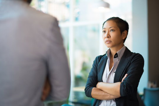 Tense Asian businesswoman looking at male partner with crossed arms. Two colleagues confronting each other in office space. Clashing personalities concept