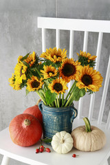 Fototapete - Bouquet of sunflowers and colorful pumpkins on white wooden chair.