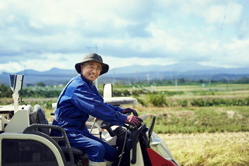 Smiling man driving tractor in field