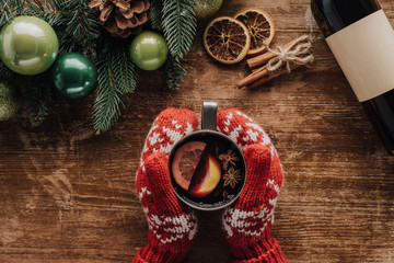 cropped image of woman holding cup of mulled wine at wooden table with christmas fir twigs