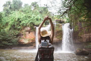 Rear view of young woman standing in front of waterfall with her hands raised. Female tourist with her arms outstretched looking at waterfall