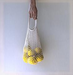 Hand holding mesh shopping bag with lemons.