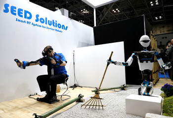 A staff member operates SEED Solutions' SEED-Noid R7 by remote-control during its demonstration at World Robot Summit in Tokyo