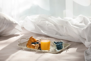 Tray with delicious breakfast on bed