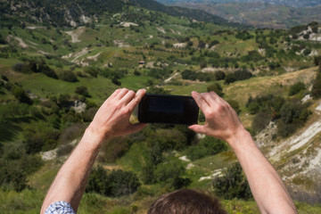 Male tourist and traveler in the mountains at the weekend travels with a telecommunication gadget. Makes landscape photos on your smartphone