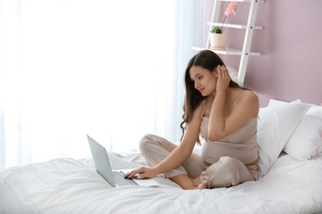 Beautiful pregnant woman with laptop in bedroom