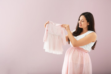 Beautiful pregnant woman with baby dress on color background