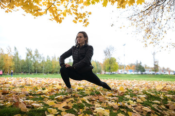 Autumn photo of sporty Young woman in black jacket stretching in forest at morning against background of trees