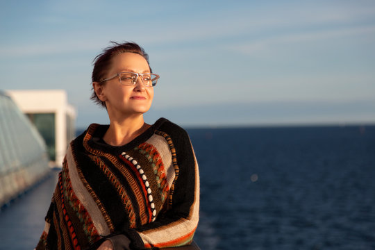 Nice portrait of an older woman looking out to the sea and cruising on a cruise ship. Beautiful middle aged lady wearing colorful jumper /poncho and standing on a cruise ship deck on sunny day.