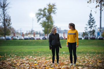 Two girls having rest after jogging in autumn park and smiling
