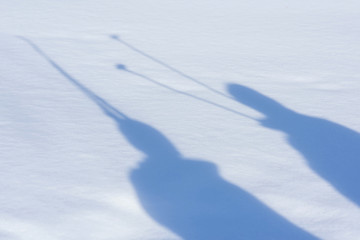 Shadow of people with skis on the snow. Winter concept