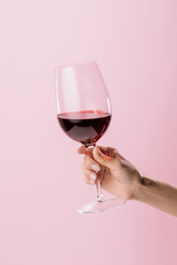 cropped shot of woman holding glass of red wine isolated on pink