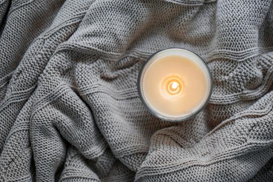 Beautiful burning candle on warm plaid